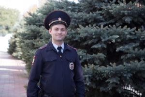 полицейский стоит возле елок и улыбается