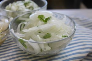 салат из лука с зеленью в тарелке