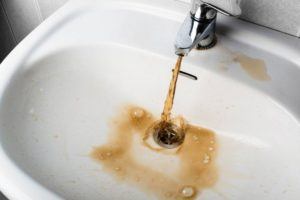 из крана в раковину течет грязная вода
