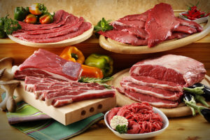 сырое мясо нескольких видов с овощами на столе