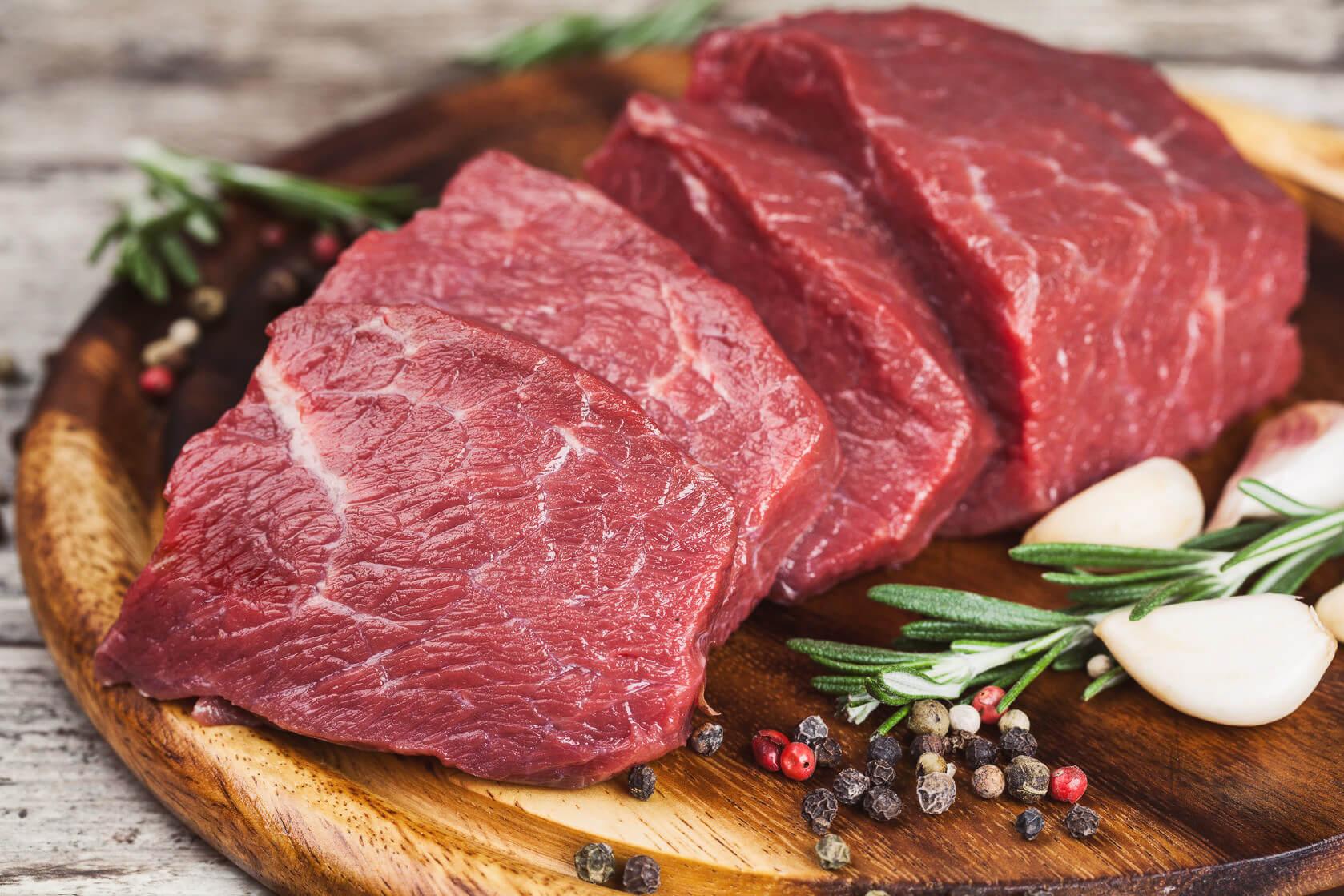 сырое мясо с перцем и розмарином на доске